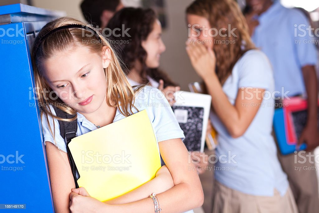 Insecure teenager at school with girls gossiping royalty-free stock photo