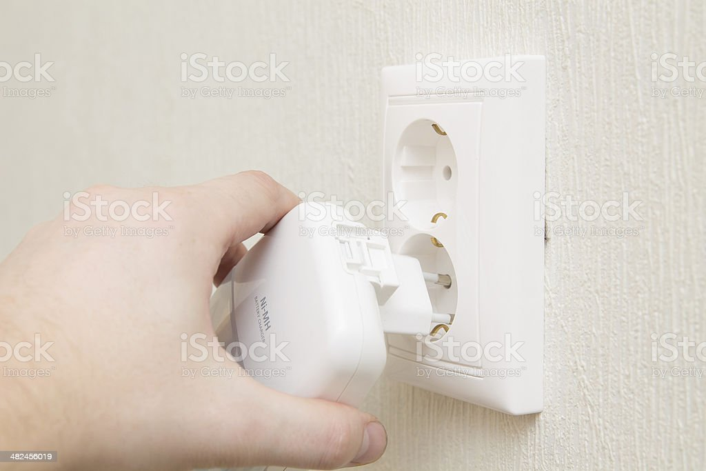 insert charger into wall outlet royalty-free stock photo