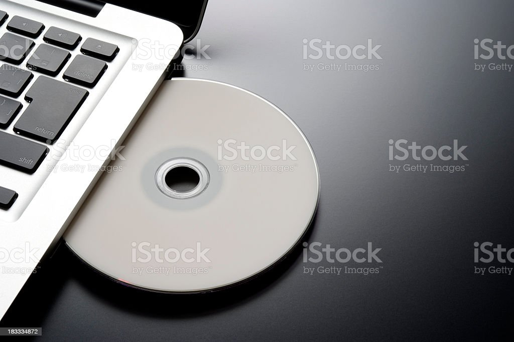 Inserting a blank CD into a laptop with copy space stock photo