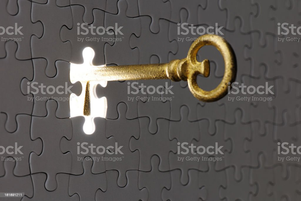 Inserting an antique skeleton key in a blank jigsaw puzzle stock photo