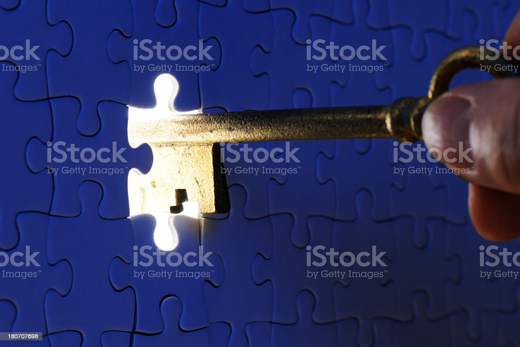 Inserting an antique skeleton key in a blue jigsaw puzzle stock photo
