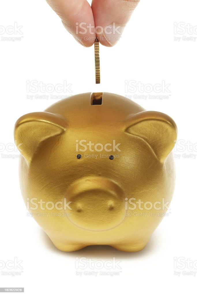 Inserting coin in a golden piggy bank royalty-free stock photo