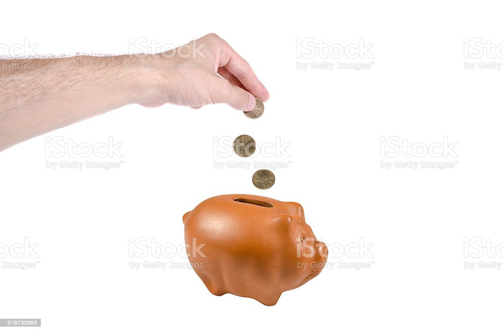 Inserting money into piggy bank stock photo