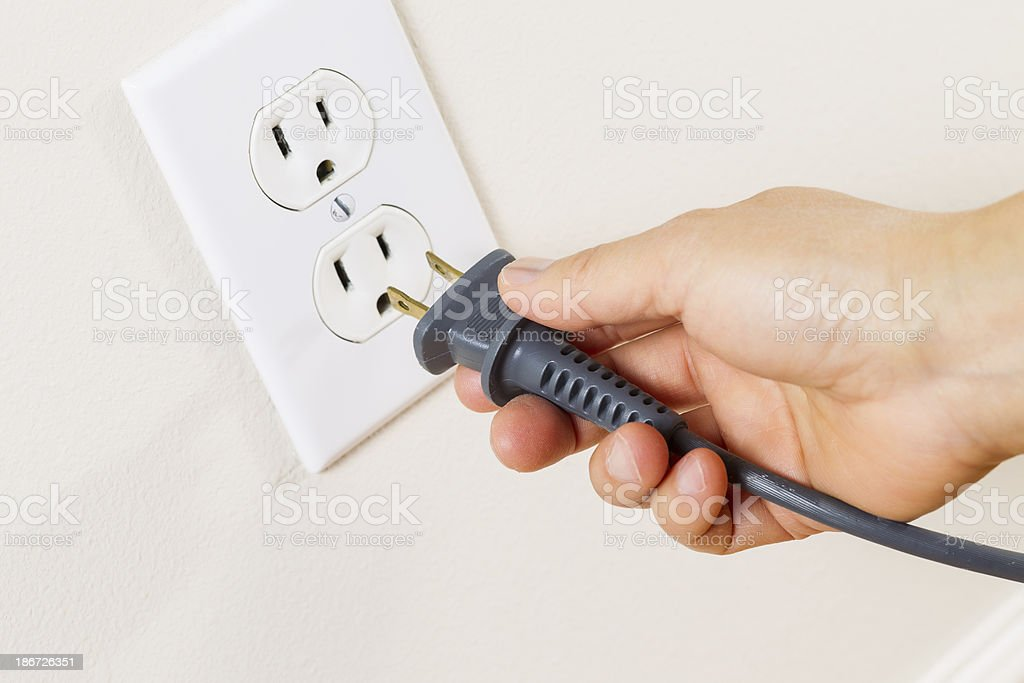 Inserting Power Cord Receptacle in wall outlet stock photo
