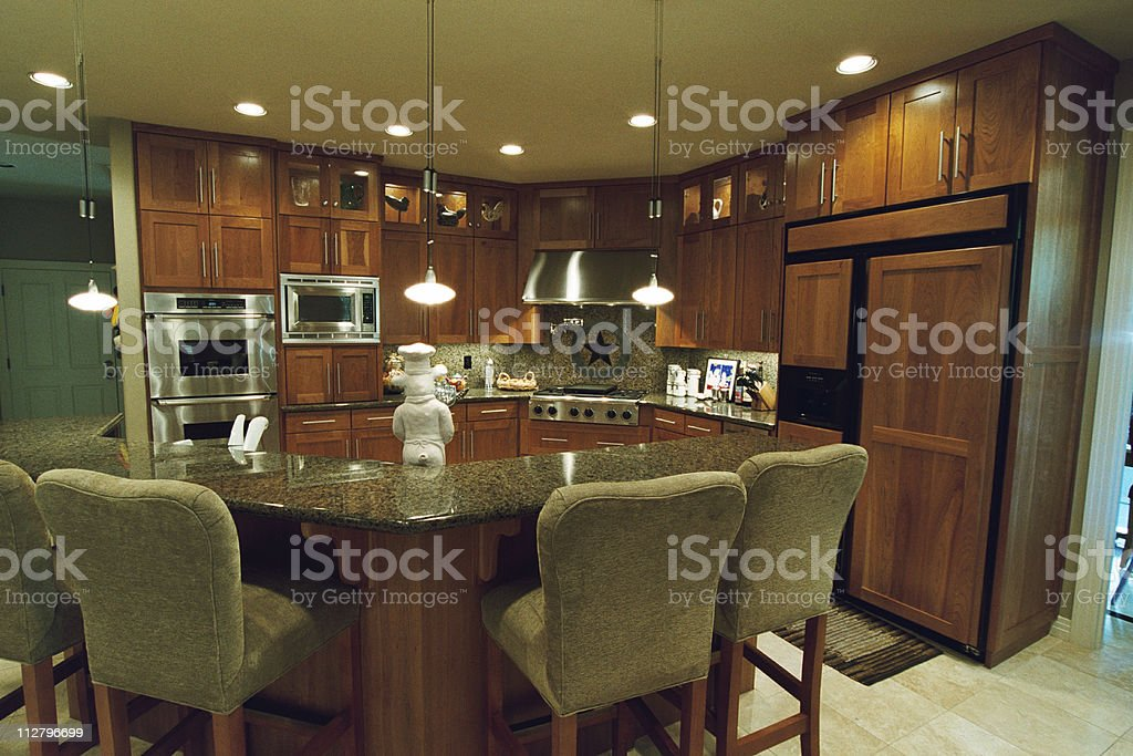 Inside a modern kitchen around the island marble counter top royalty-free stock photo