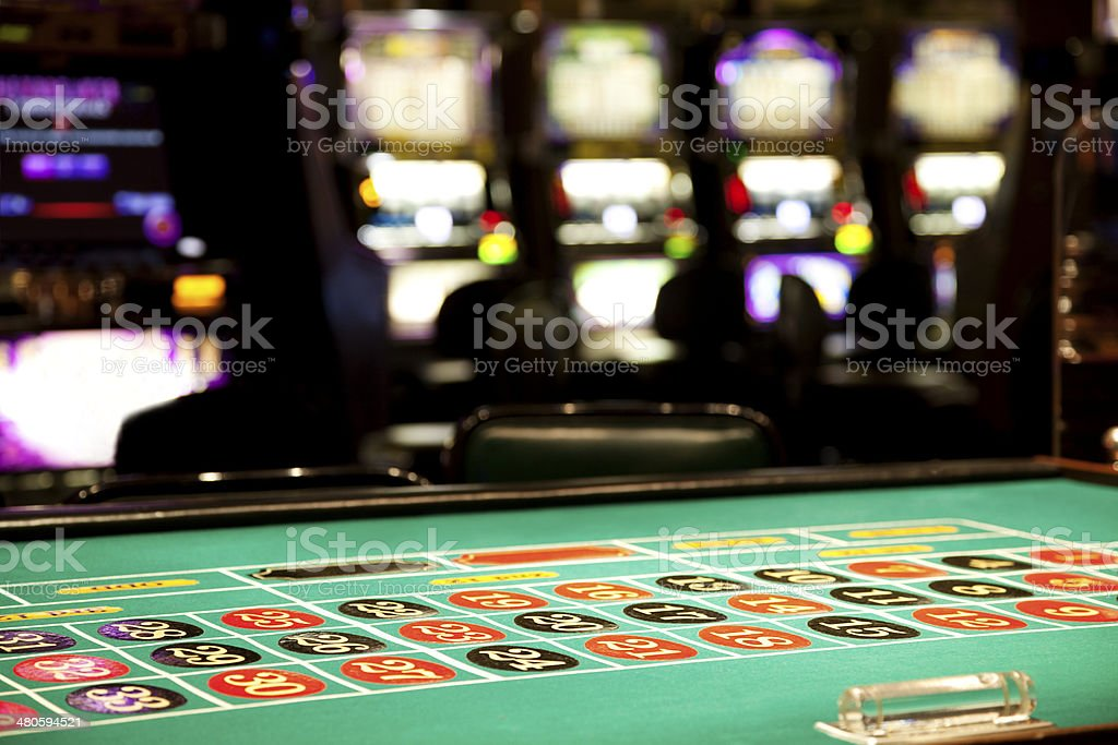 Inside of a casino, roulette table and slot machines stock photo