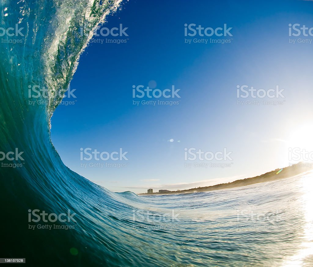 Inside of a curved wave on the sea at sunrise royalty-free stock photo