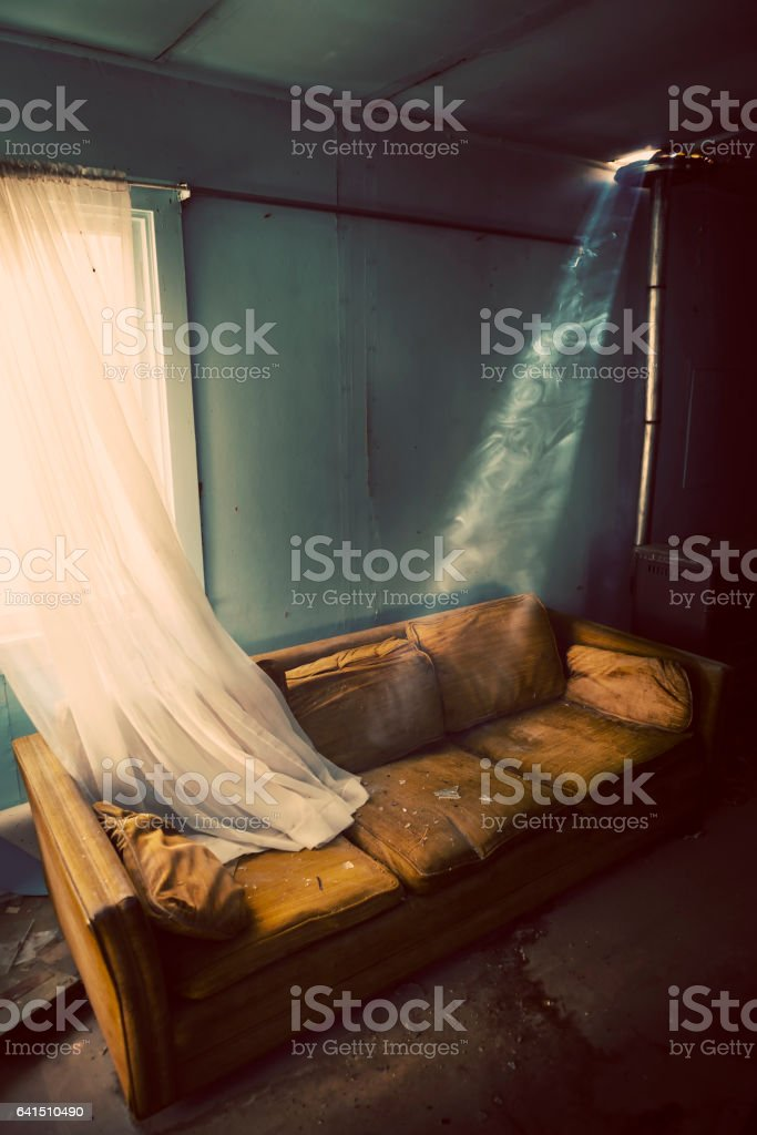 Inside old living room with broken glass and worn out couch. Image is...
