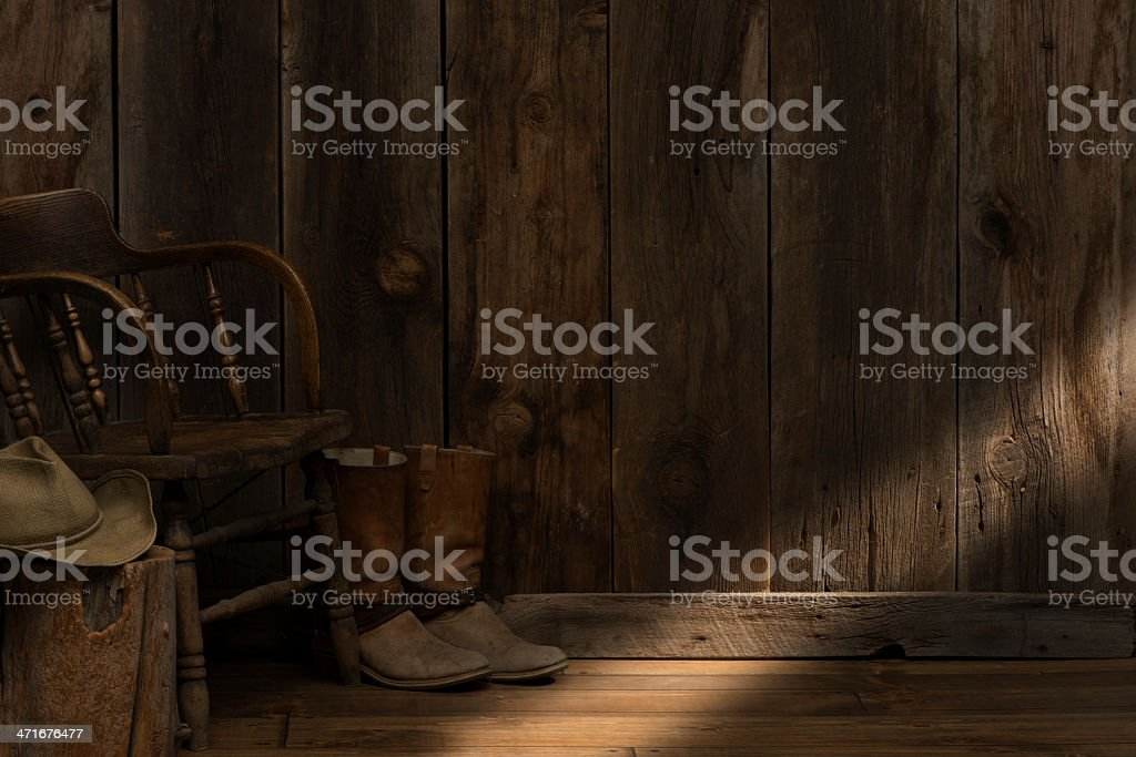 Inside Western barn w/cowboy boots,hat,chair,sunbeam-copy space royalty-free stock photo