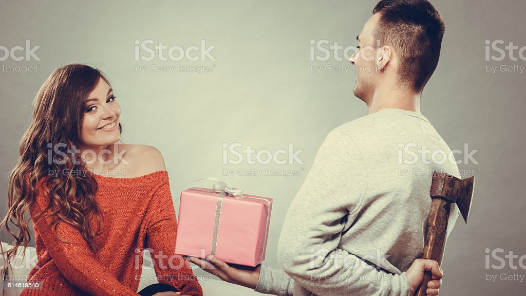 Insincire man holding axe giving gift box to woman stock photo