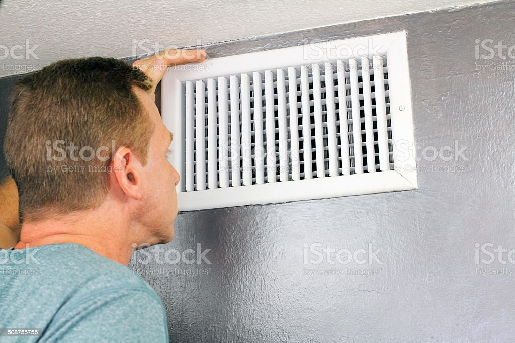 Inspecting a Home Air Vent for Maintenance stock photo