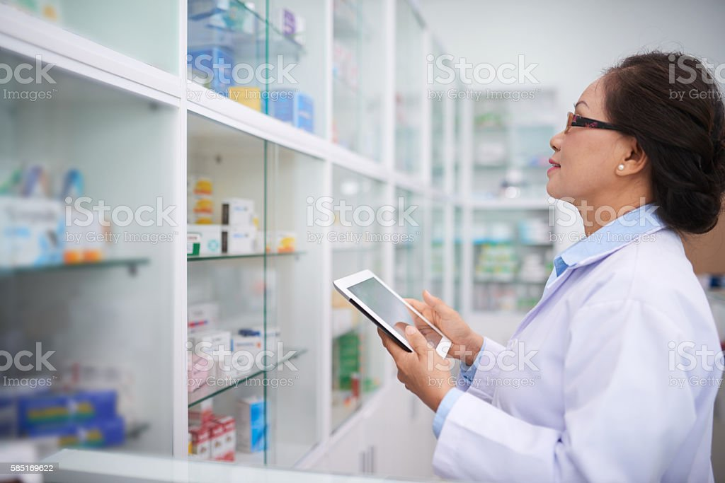 Pharmacist with tablet computer inspecting shelves with medications