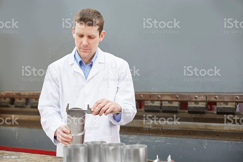 Inspector checking finished pieces of metalwork stock photo