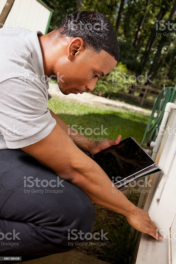 Inspector, engineer examines building wall, foundation outdoors. stock photo