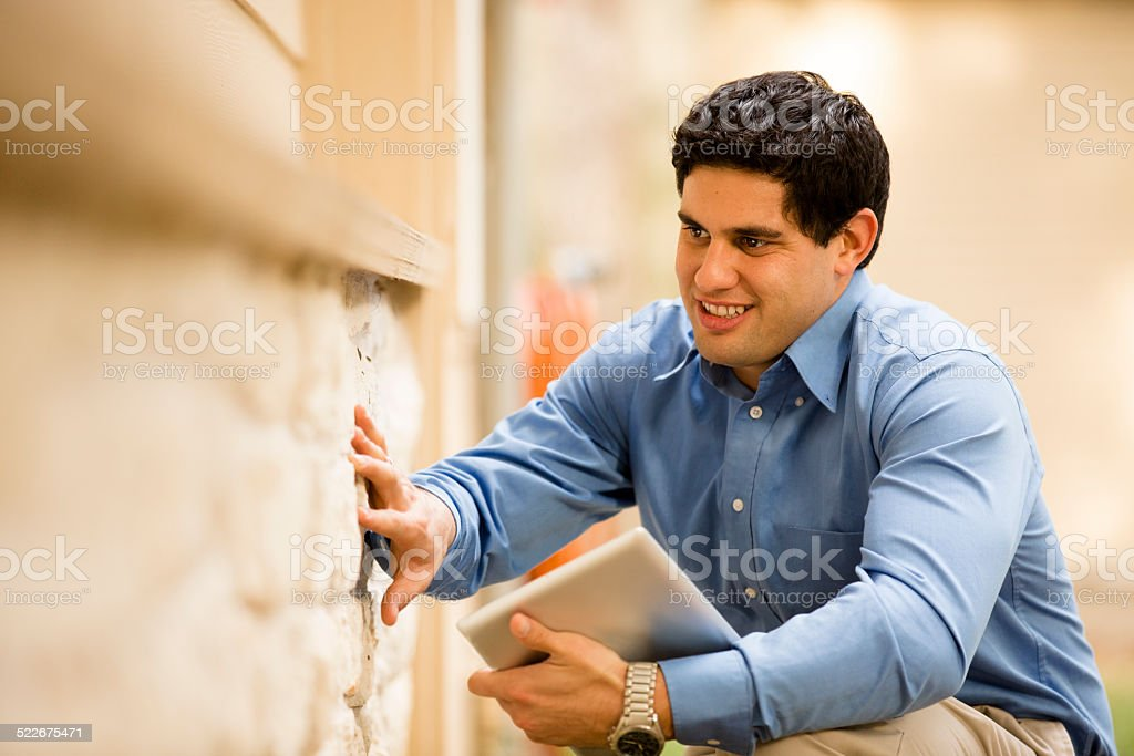 Inspector, engineer examines building wall outdoors. Latin descent. Digital tablet. stock photo