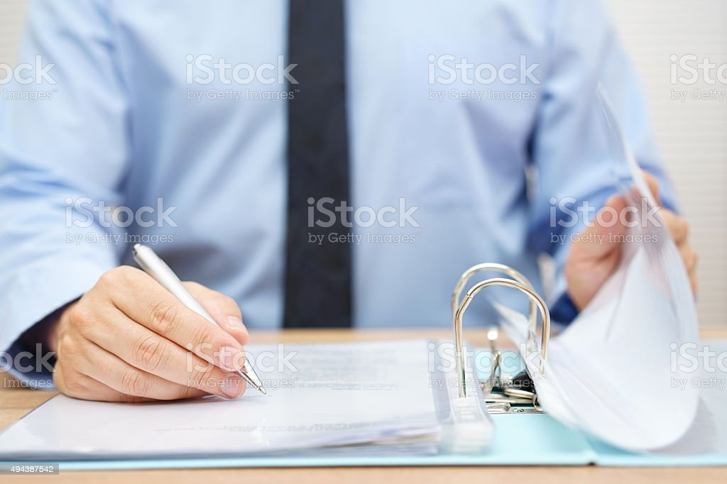 inspector is .reviewing invoices in binder stock photo