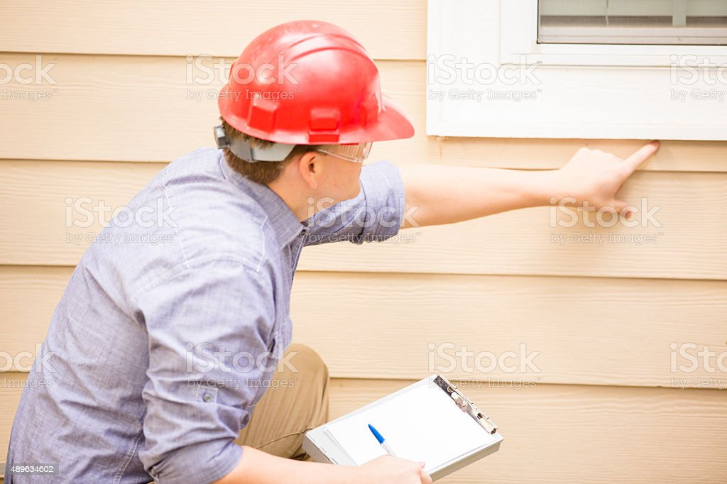 Inspector or blue collar workers examines building wall, window. Outdoors. stock photo