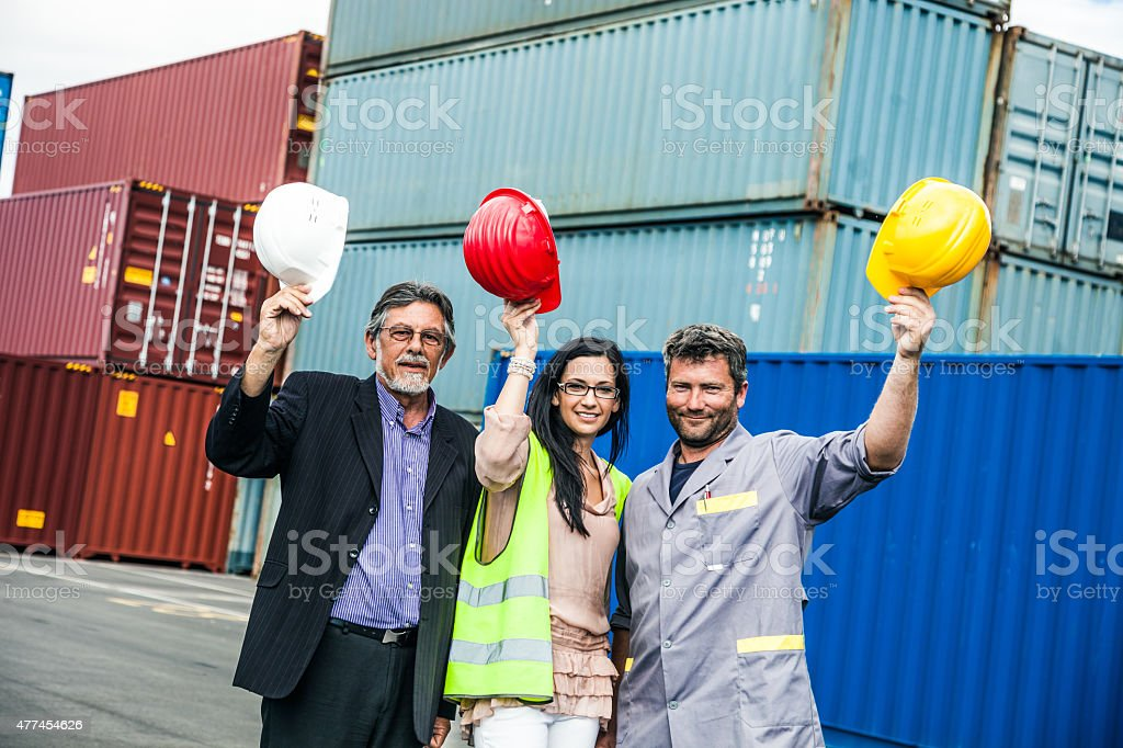 Inspectors and workers at commercial dock waving with helmets stock photo
