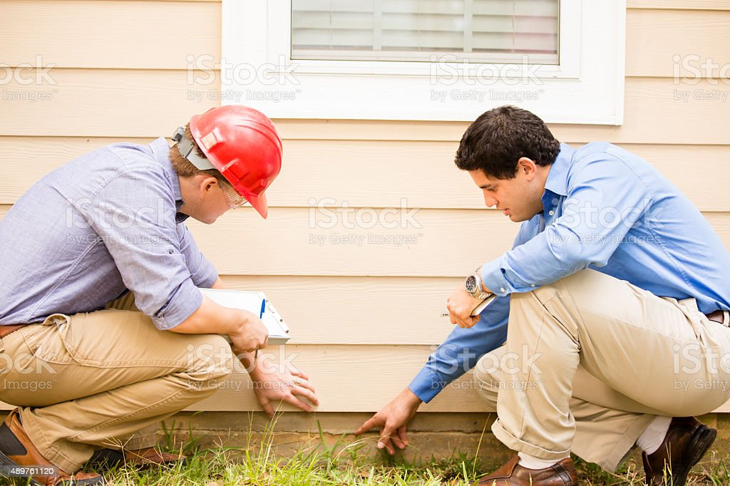 Inspectors or blue collar workers examine building wall, foundation. Outdoors. stock photo