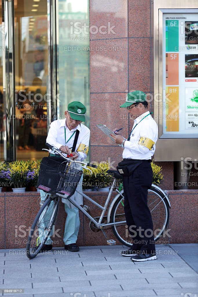 Inspectors putting violation sticker on illegal parking bicycle stock photo