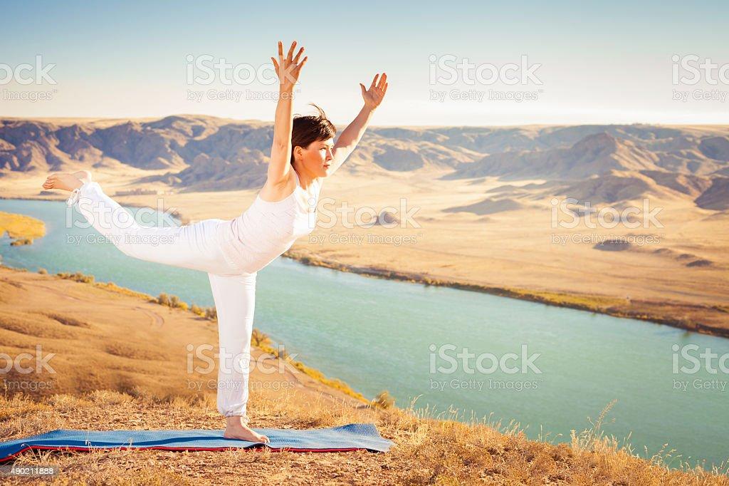 Inspired asian woman doing exercise of yoga at mountain range stock photo