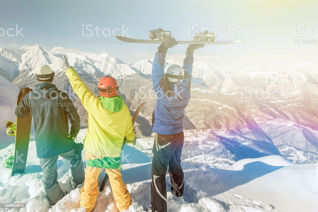Inspired group of snowboarders at summit stock photo