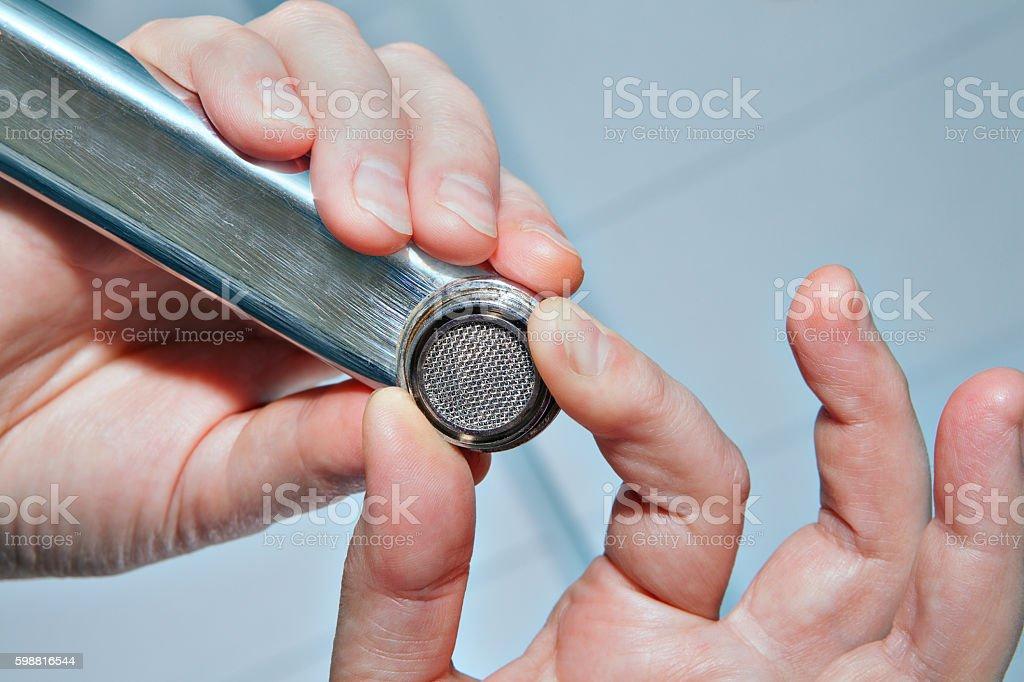 Install tap aerator, tighten the nut, close up. stock photo