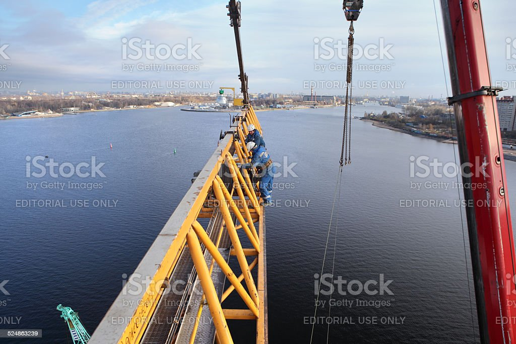Installation of tower crane on construction site, workers steeplejacks working. stock photo