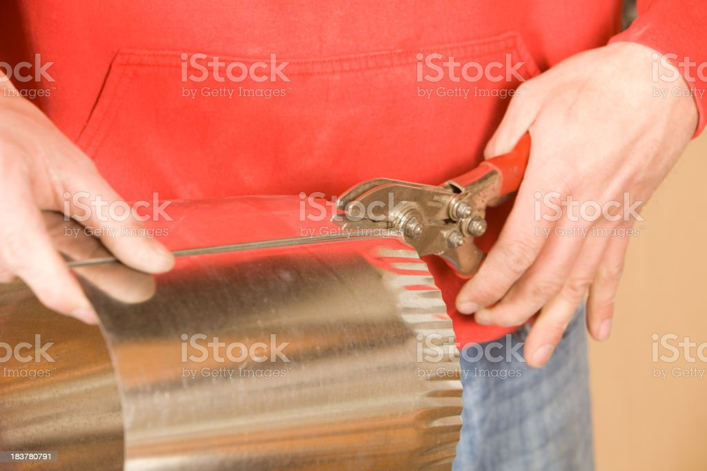 HVAC Installer Crimping Round Duct for Residential Installation stock photo