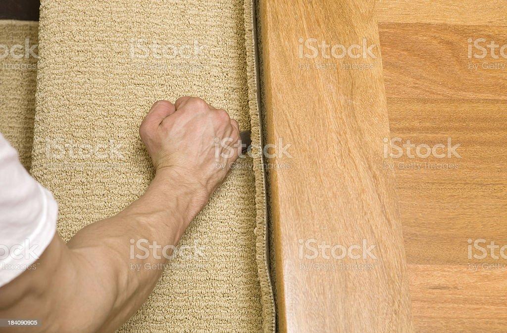 Installer Cutting Carpet Stair Tread Near Hardwood Landing stock photo