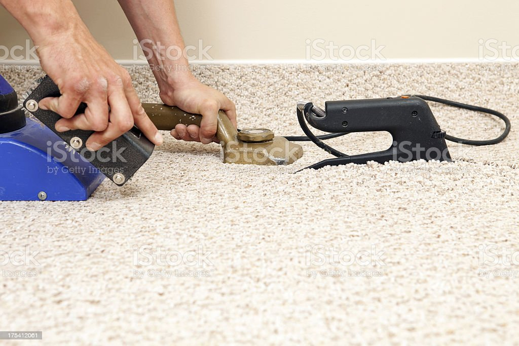 Installer Joining Two Carpet Pieces with Iron stock photo