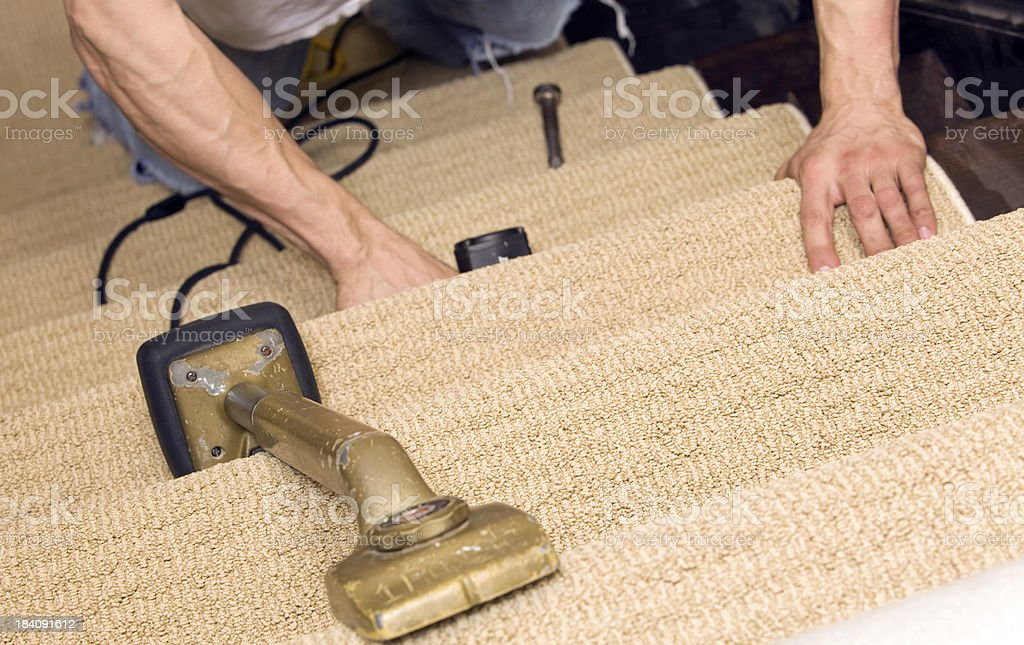 Installer Stapling Stair Carpet with Knee Kicker in the Foregrou stock photo