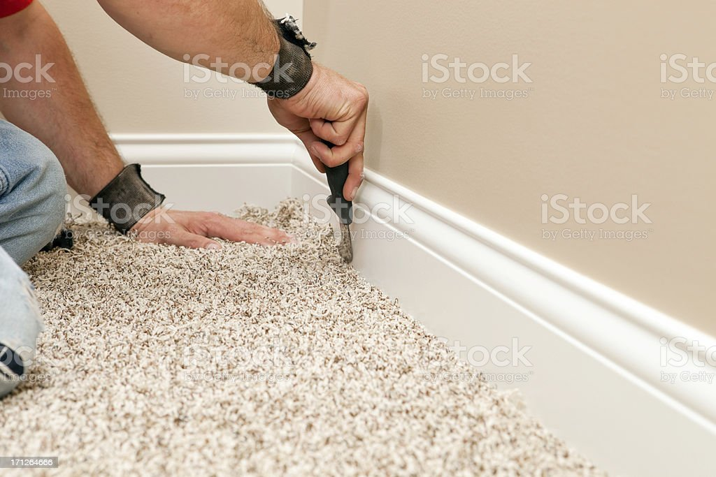 Installer Using Carpet Knife to Tuck New Floor stock photo