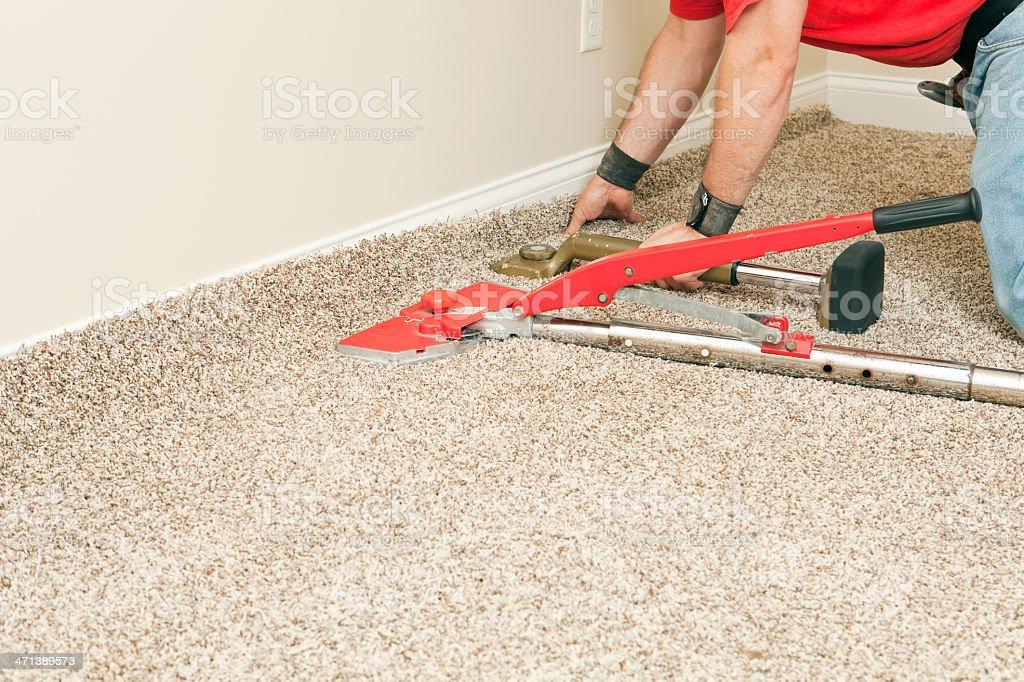 Installer Using Carpet Stretcher on New Bedroom Floor stock photo