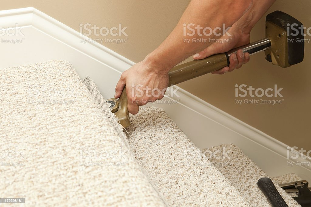 Installer Using Carpet Stretcher on Stairs stock photo