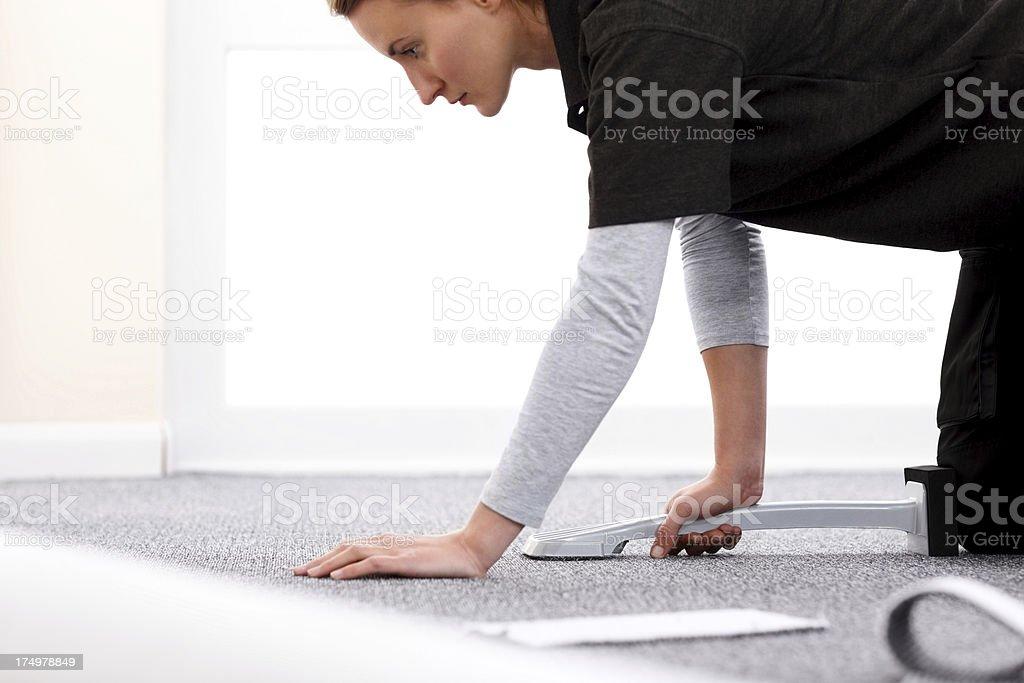 Installer using carpet stretcher stock photo