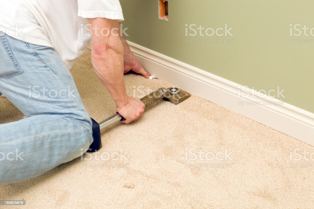 Installer Using Knee Kicker to Stretch Bedroom Carpet royalty-free stock photo
