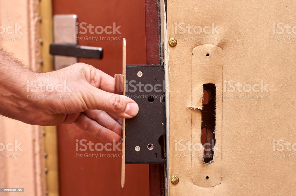 Installing a new lock into old door close up stock photo