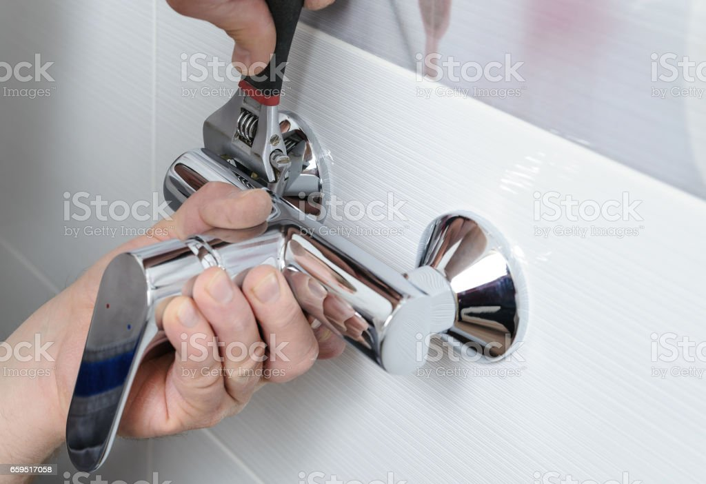 Installing a shower faucet. stock photo
