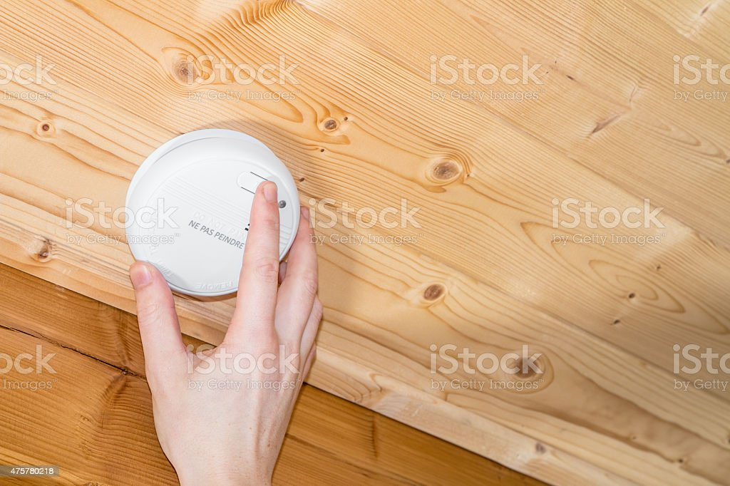 Installing and testing wood ceiling mounted home smoke detector alarm stock photo