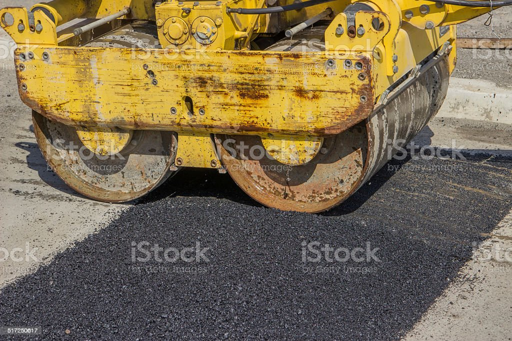 Installing asphalt speed bumps to slow down speeding drivers stock photo