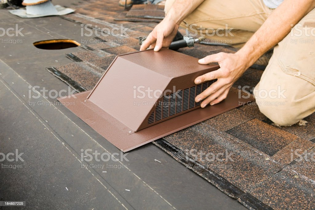 Installing Attic Vent on Home Roof Replacement Project stock photo