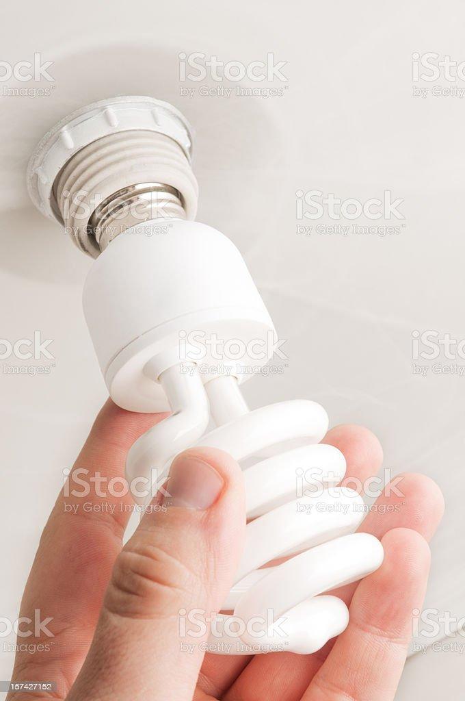 Installing CFL Bulb stock photo