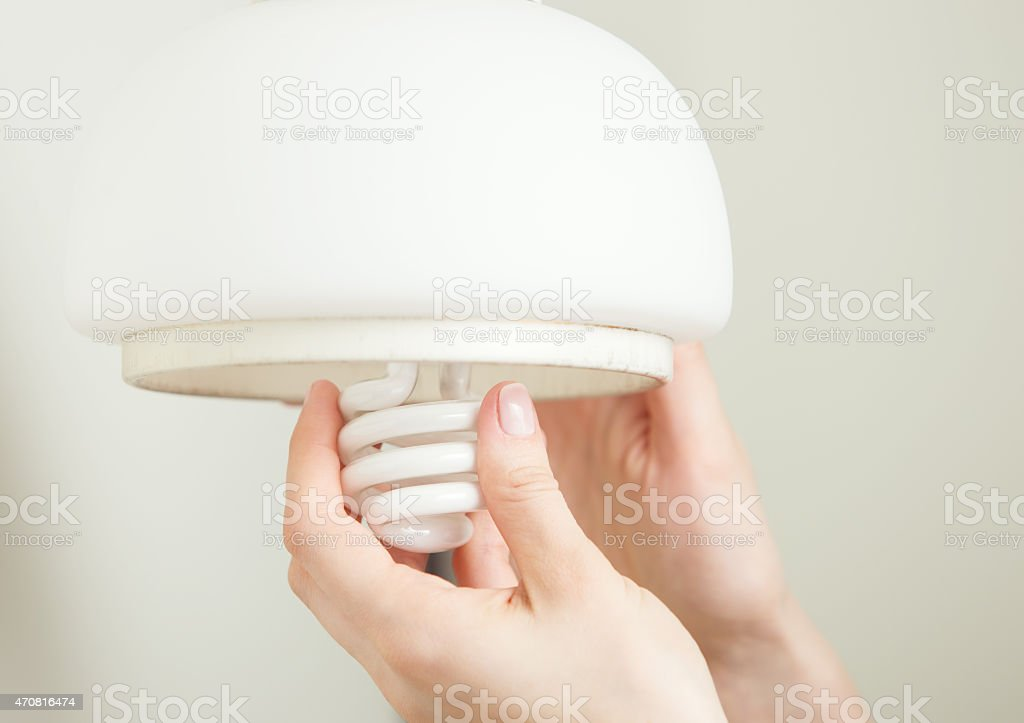 Installing energy efficient compact fluorescent light stock photo