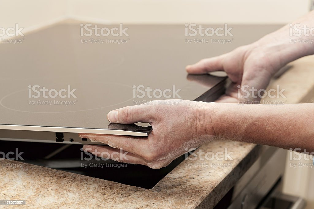 Installing induction hob royalty-free stock photo