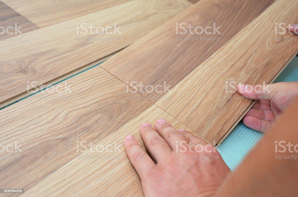 Installing laminate flooring fitting the next piece. Laminate flooring. stock photo