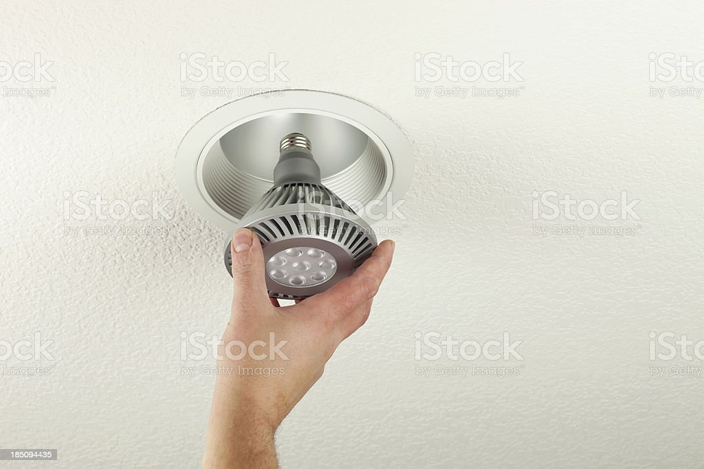 Installing LED Light Bulb into Ceiling Fixture stock photo