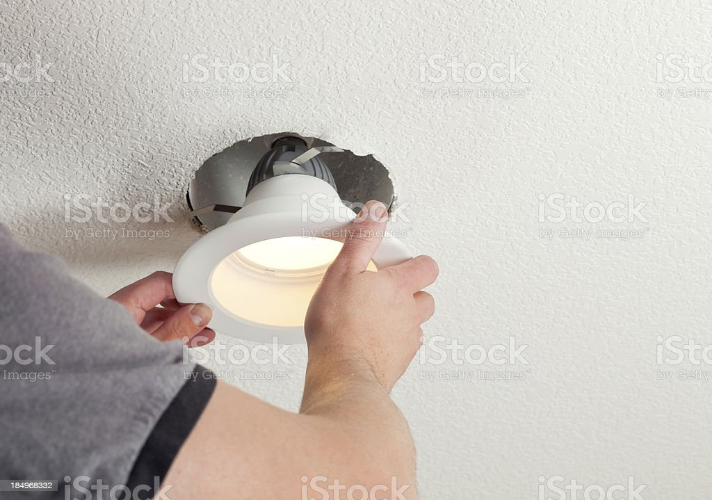 Installing LED Retrofit Bulb into Ceiling Fixture stock photo