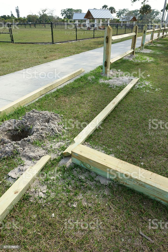 Installing pressure treated wood split rail fence stock photo