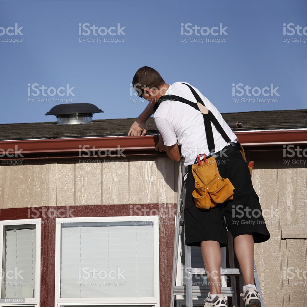 Installing Seamless Gutters on Home stock photo